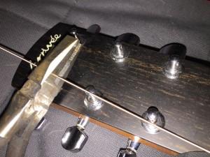 stringing a guitar - cut string